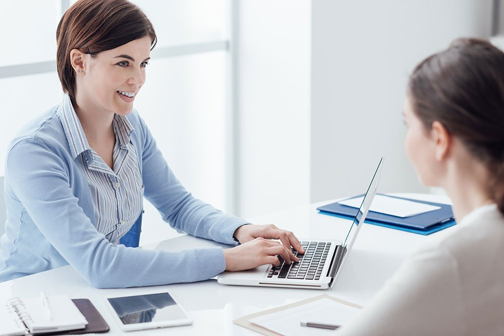 Woman meeting with another woman about payroll services working on a computer