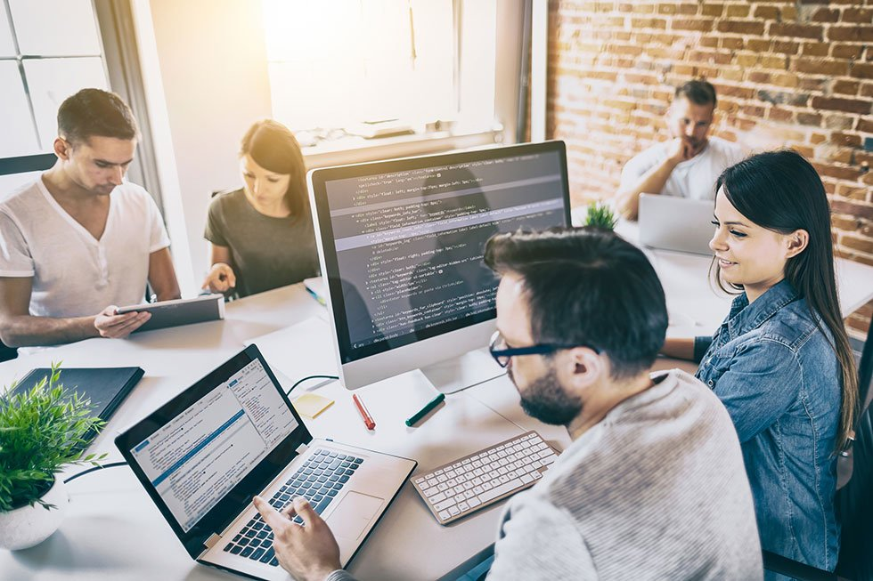 Group of people working together on computers doing payroll services