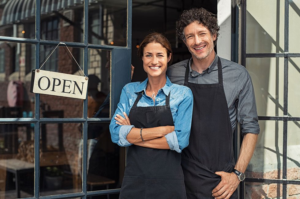 woman and man standing in front of shop with open sign saving time while we are doing their payroll services