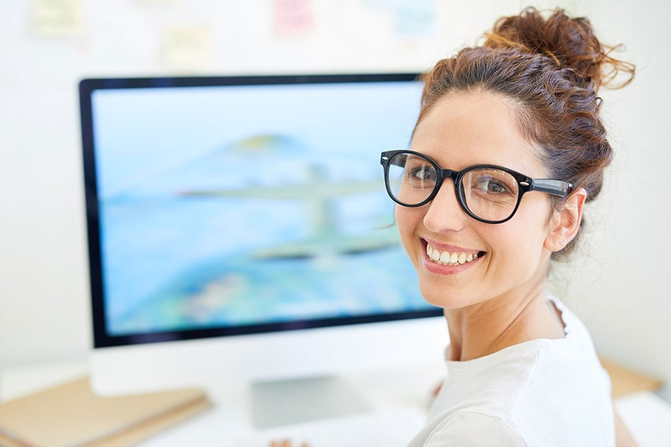 Lady smiling infront of a computer providing payroll services