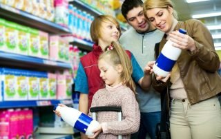 family of 4 standing in grocery store looking at milk bottles