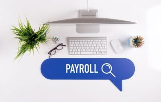 over the top view of a work desk with payroll written in blue with a magnifying glass