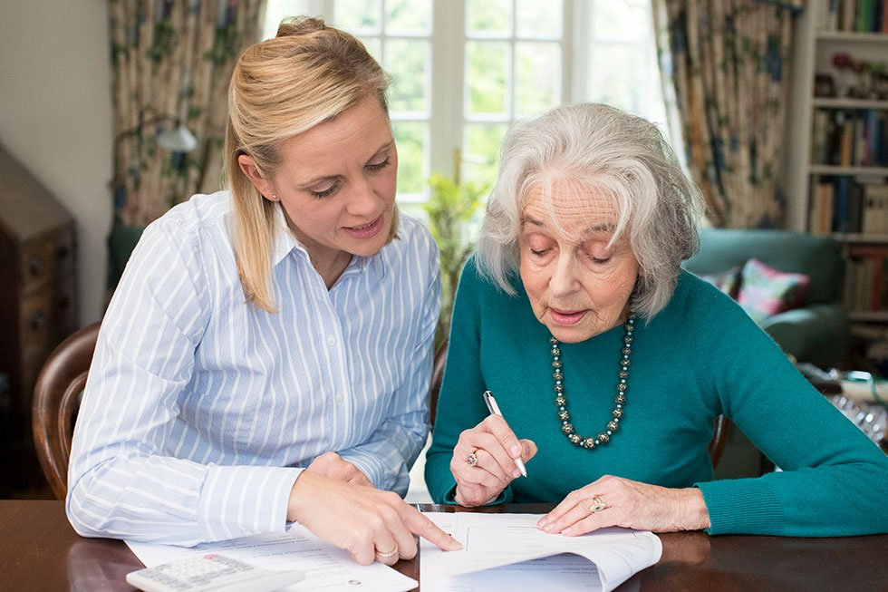 older lady and younger lady reading a document together