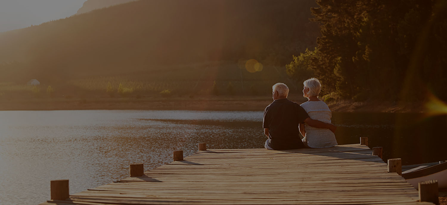 older couple relaxing by the lake