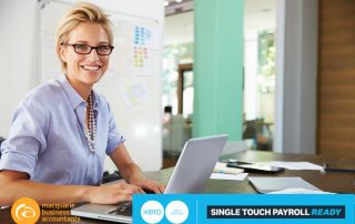 woman smiling sitting at desk working on a laptop