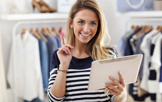 woman standing in clothing store holding an ipad