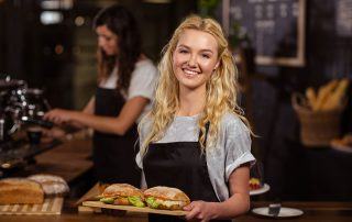 young waitress smiling and carrying food