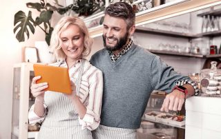 couple standing in cafe smiling at ipad