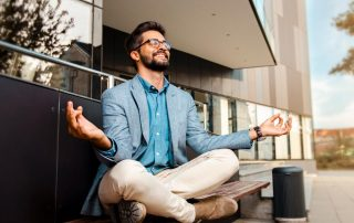 man in office clothes meditating on seat