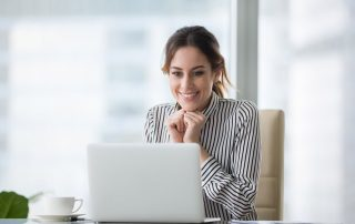 lady in office clothes at desk smiling at laptop