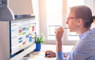 lady holding pen to mouth looking at computer calendar