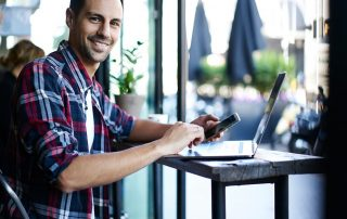 man in casual clothing smiling at laptop holding mobile phone