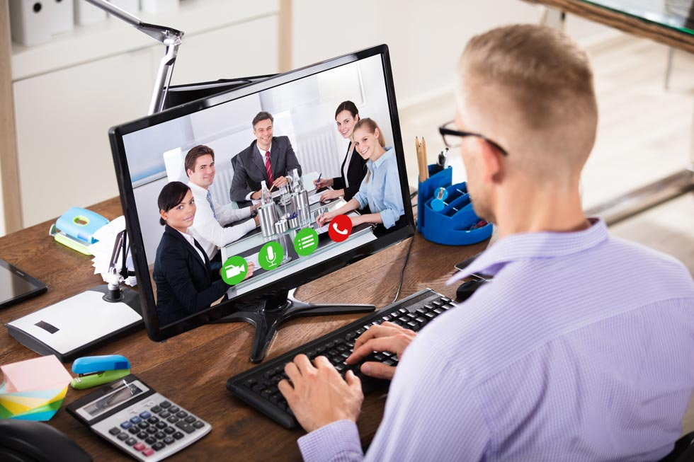 man meeting with colleges over video conference
