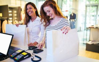 young women with shopping bags smiling using EFTPOS machine to pay for goods