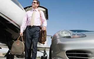 business man with briefcase walknig between a plane and car