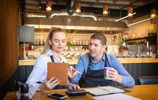 Young couple in cafe smiling over paperwork and calculator
