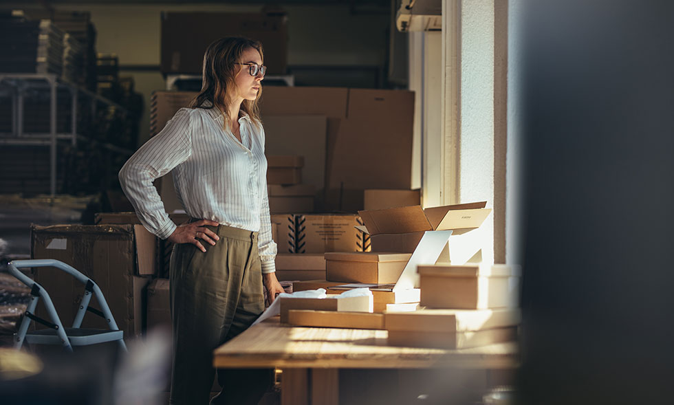 female business owner looking out window in shadowy office
