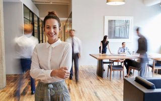 casual office worker smiling while people are in background