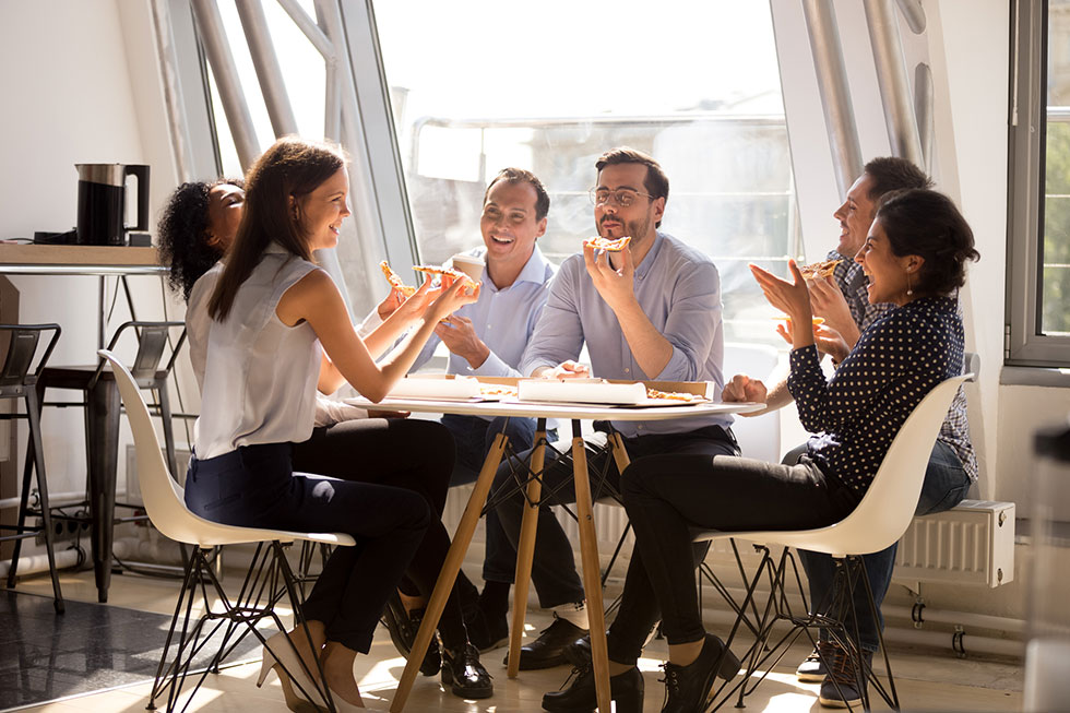 office staff sitting around a table laughing eating pizza
