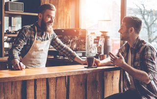 barista and customer talking at cafe smiling looking relaxed