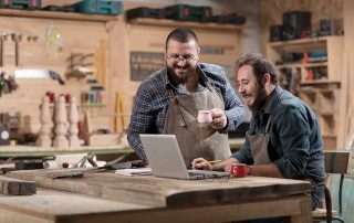2 tradesman in workshop with coffee smiling over laptop