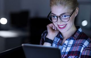 young woman amused smiling at laptop