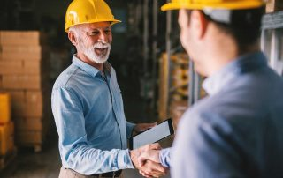 2 men wearing yellow hard hats in back dock shaking hands