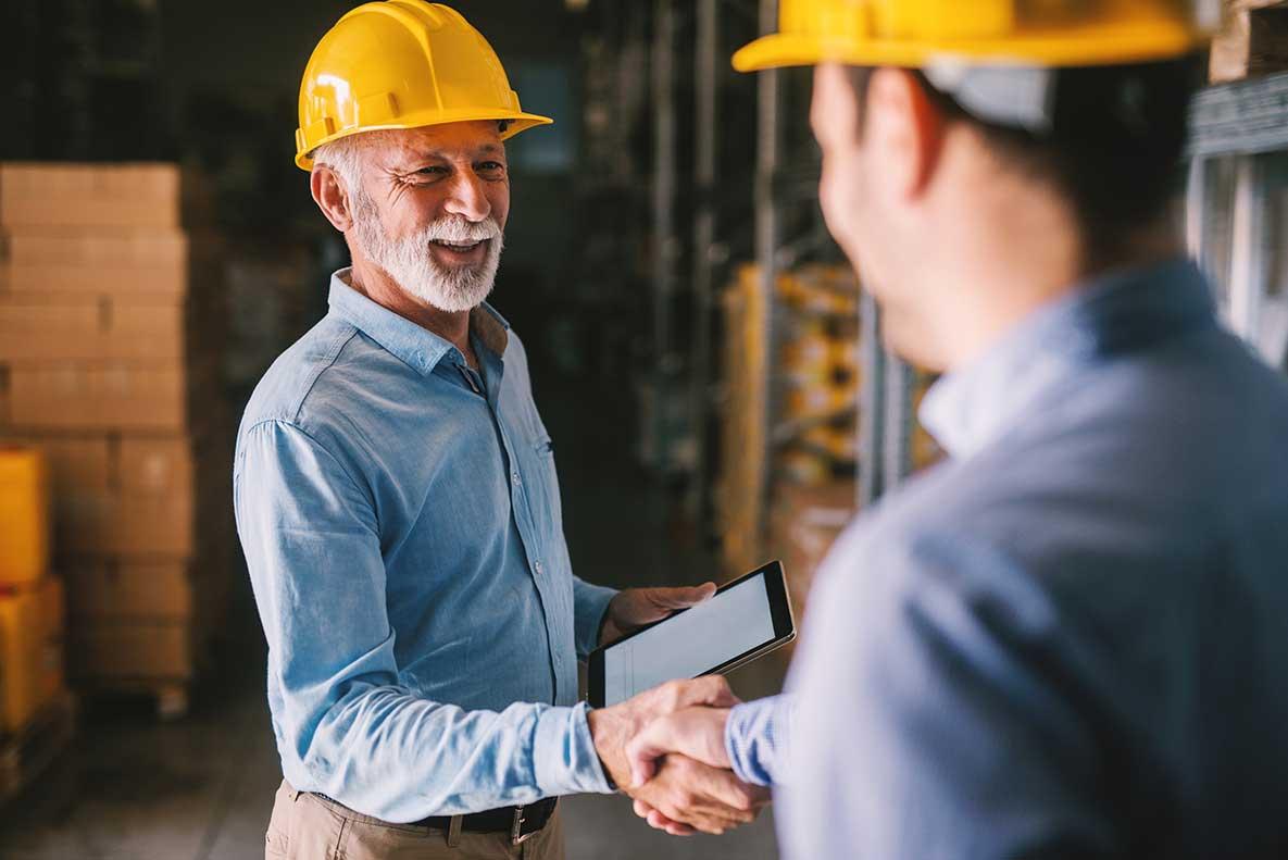 2 men wearing yellow hard hats in back dock shaking hands