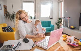 mother working from home sitting at desk with baby scrunching up papers