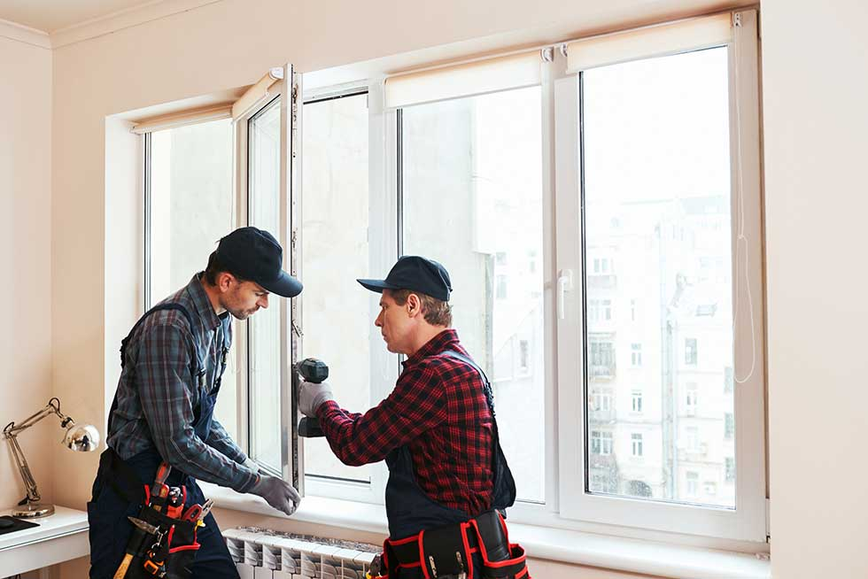 2 tradesman with tools fixing a window