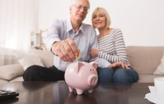 senior couple sitting on lounge putting coin in a piggy bank