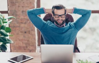 man in casual office attire smiling at laptop with hands rested behind his head