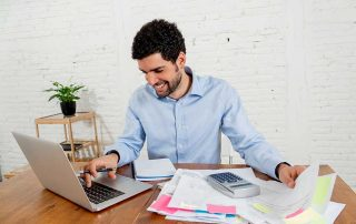 professional man sitting at desk smiling while using a laptop and looking through paperwork