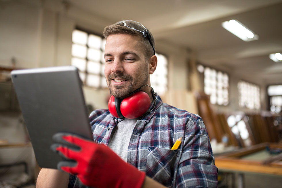 man in workshop with gloves and earmuffs on holding an ipad and smiling