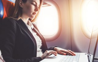business women sitting next to air plane window with laptop in lap