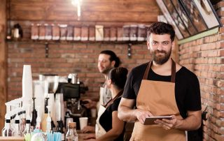 man in apron standing in front of 2 staff in cafe holding an ipad