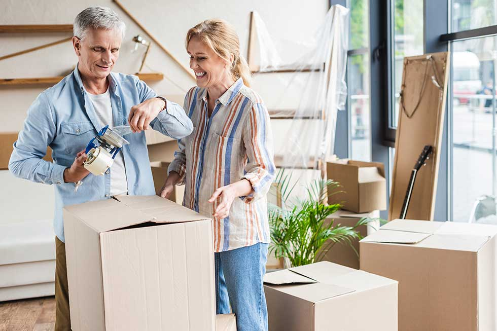 senior couple smiling while packing moving boxes in their home