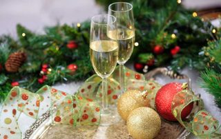 green red and gold Christmas decorations on a table with two glasses of champagne