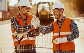 two tradesman in fluro shirts and safety clothes shaking hands and smiling in front of machinery