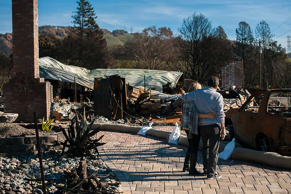 couple with arms around each other looking a burned property