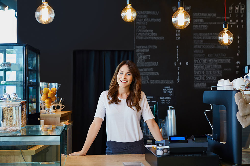 young woman smiling behind counter in a cafe