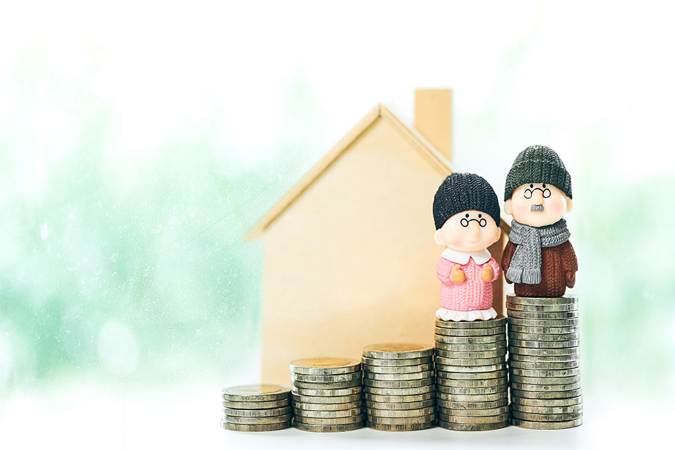 figurines of elderly couple standing on coins in front of wooden house