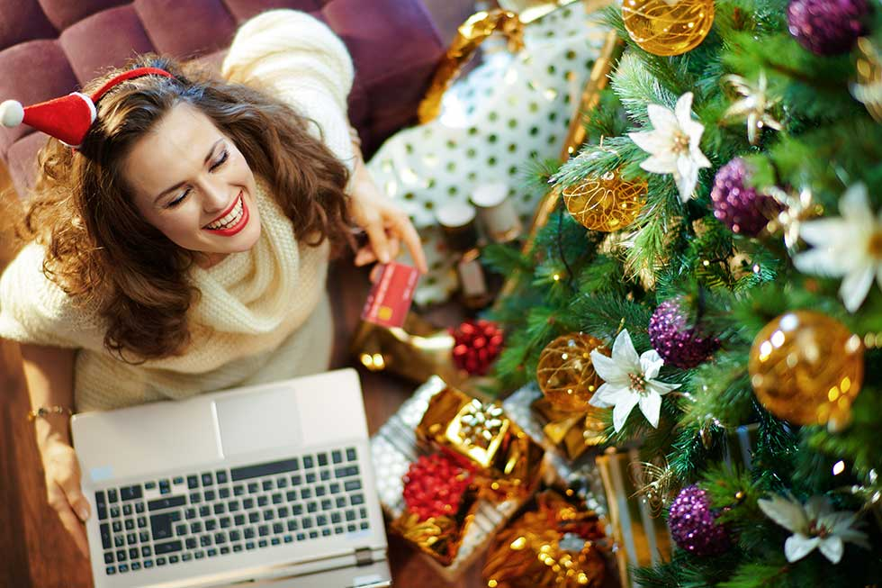 pretty woman sitting in front of Christmas tree smiling on a laptop holding credit card