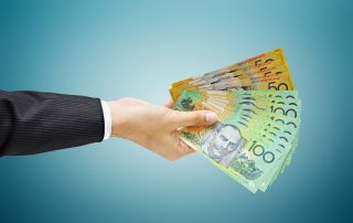 male arm showing suit jacket handing out AustrALIAN CURRENCY NOTES