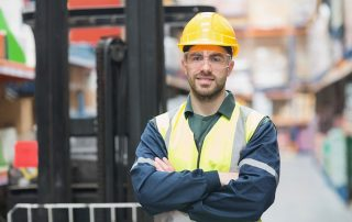 Adult Man in fluro work clothes and hard hat standing with arms folded smiling in warehouse