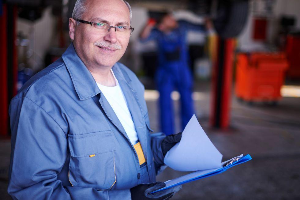 Older mechanic standing with clipboard in workshop