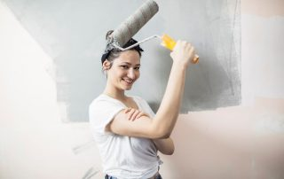 young women smiling painting a wall with roller