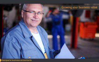 Senior man in workshop holding papers smiling